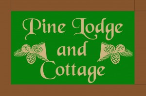 Pine Lodge and Cottage - The house sign is on a post by the front gates.